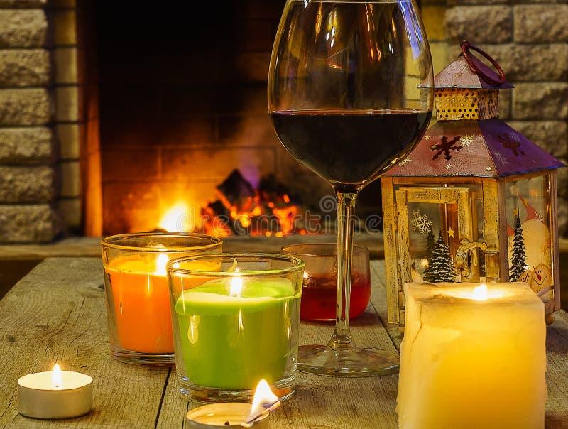 杯与蜡烛和灯笼的红葡萄酒,在舒适壁炉附近 图库摄影