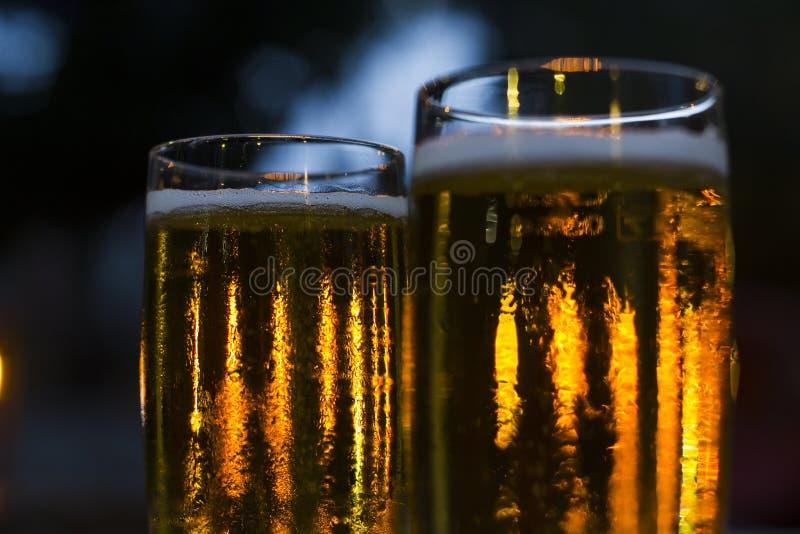 杯与被弄脏的光的啤酒在背景 免版税库存图片