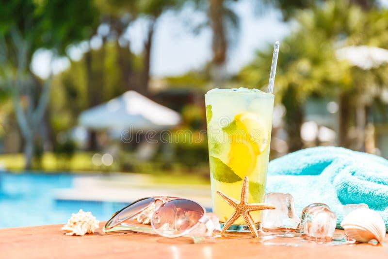 杯与贝壳、太阳镜和毛巾的经典mojito鸡尾酒 库存图片