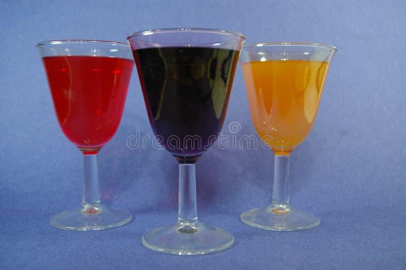 3杯五颜六色的鸡尾酒含羞草和红葡萄酒集合联合国在蓝色背景 免版税库存照片
