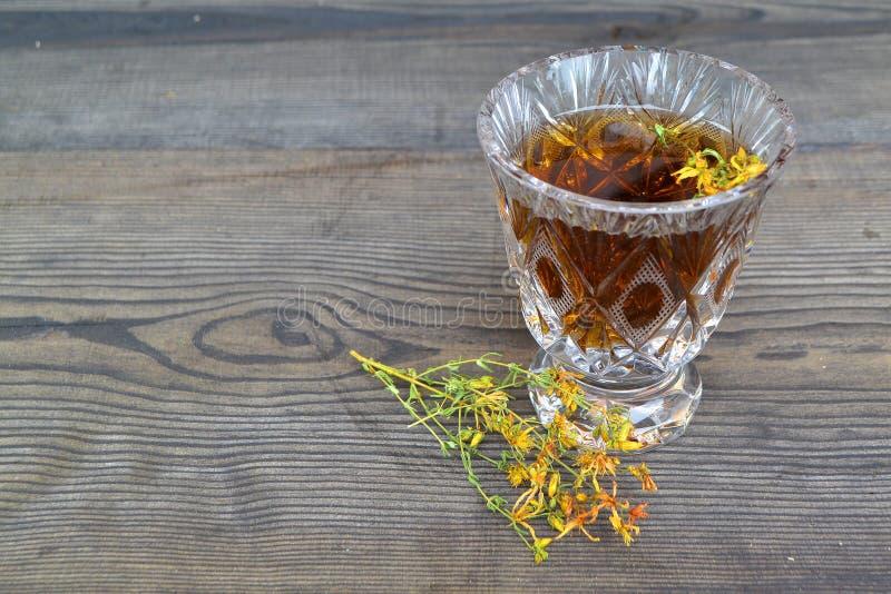杯从金丝桃属植物的清凉茶:圣Jonh的在水晶玻璃的麦芽酒草的酊或滴露在黑桌上 E 库存图片