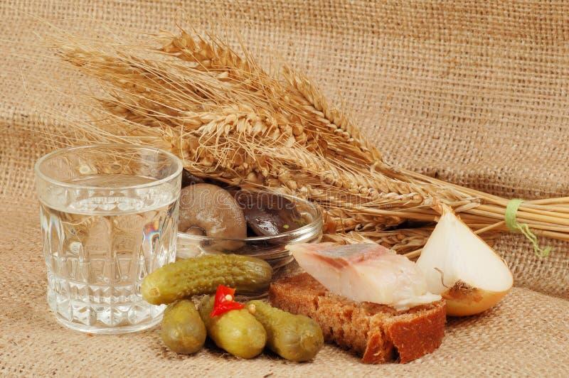杯伏特加酒和食物 免版税库存照片