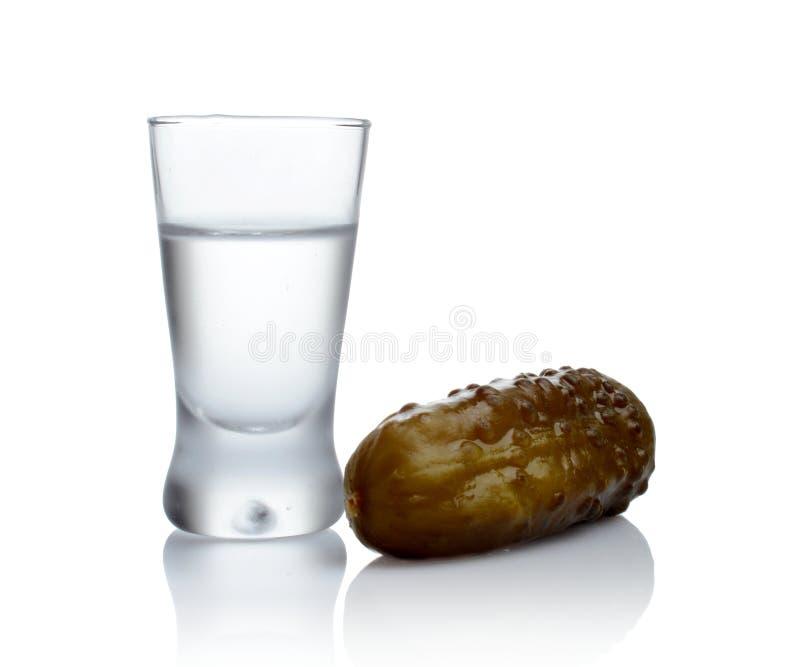 杯伏特加酒用在白色背景隔绝的酱瓜 免版税库存照片