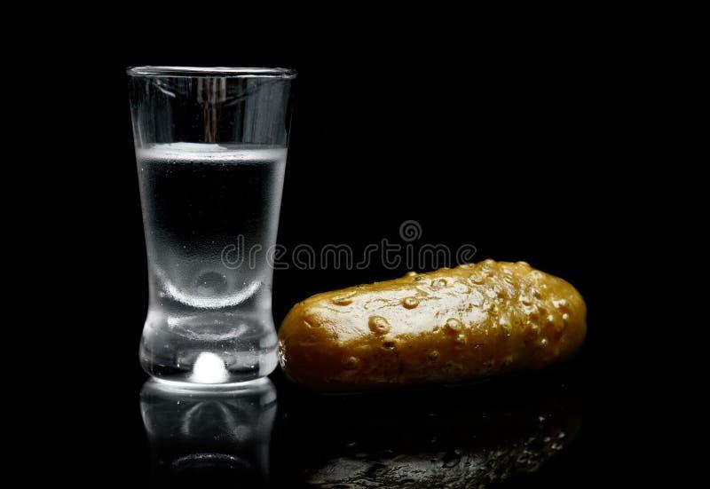 杯伏特加酒用在黑背景隔绝的酱瓜 免版税库存照片