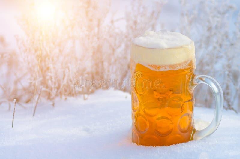 杯低度黄啤酒和泡沫在雪 库存图片