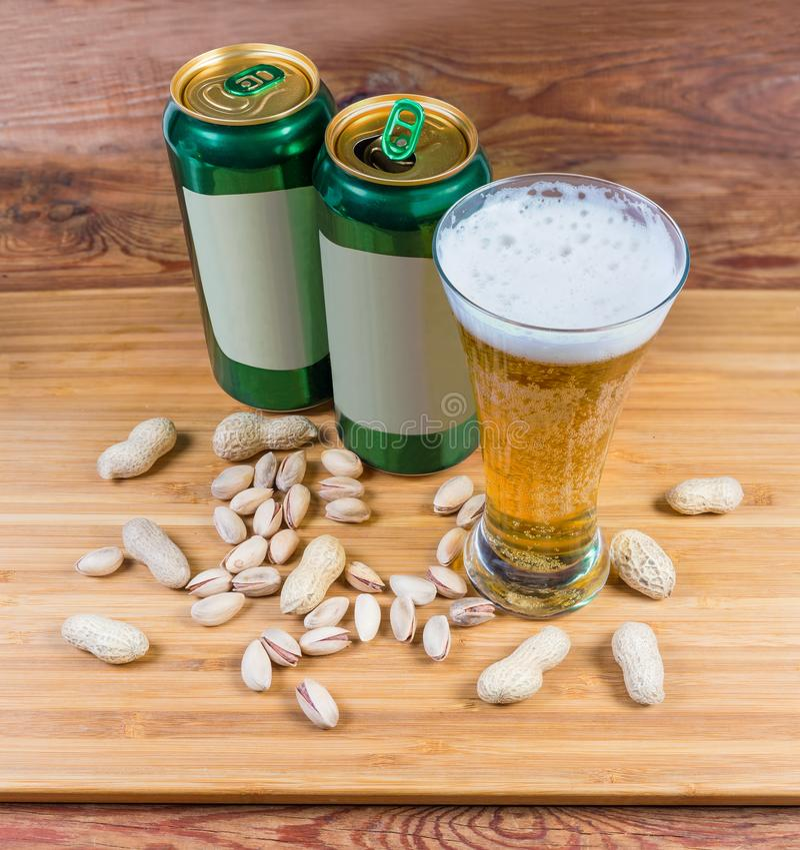 杯储藏啤酒,反对两个啤酒罐的坚果 免版税库存图片