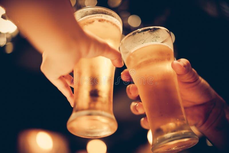 杯冰镇啤酒底部与美好的bokeh,朋友一起喝啤酒 库存图片