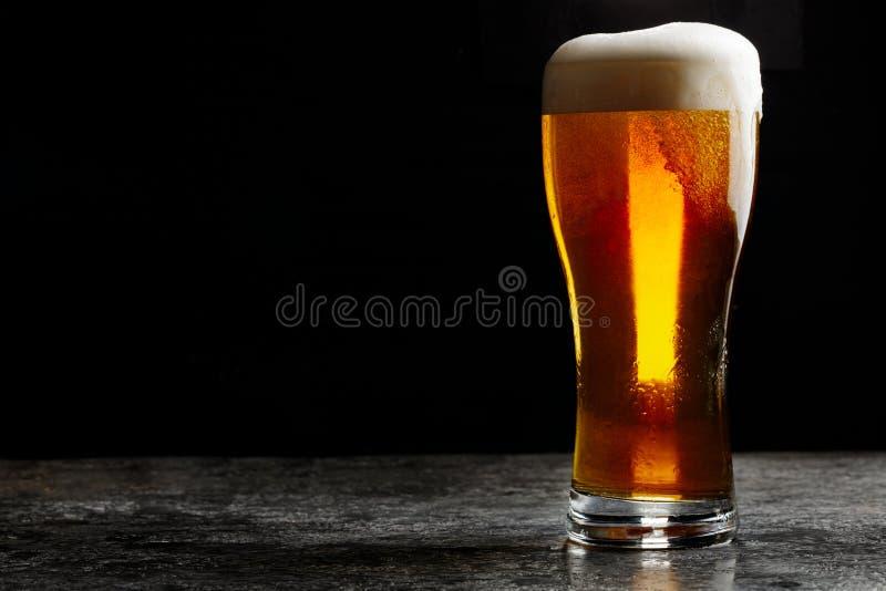 杯冷的在黑暗的背景的工艺低度黄啤酒 免版税图库摄影