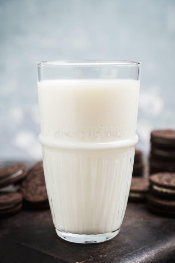 杯冷的牛奶和巧克力饼干在土气背景 免版税库存照片