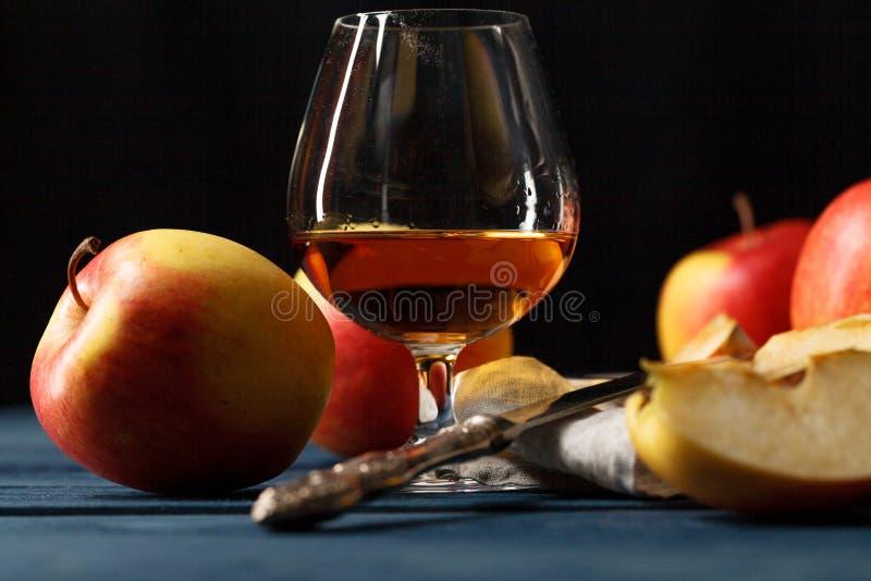 杯卡尔瓦多斯白兰地酒和红色苹果 库存图片