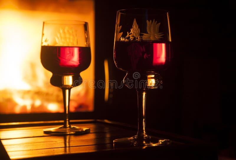 杯反对壁炉的酒 库存照片