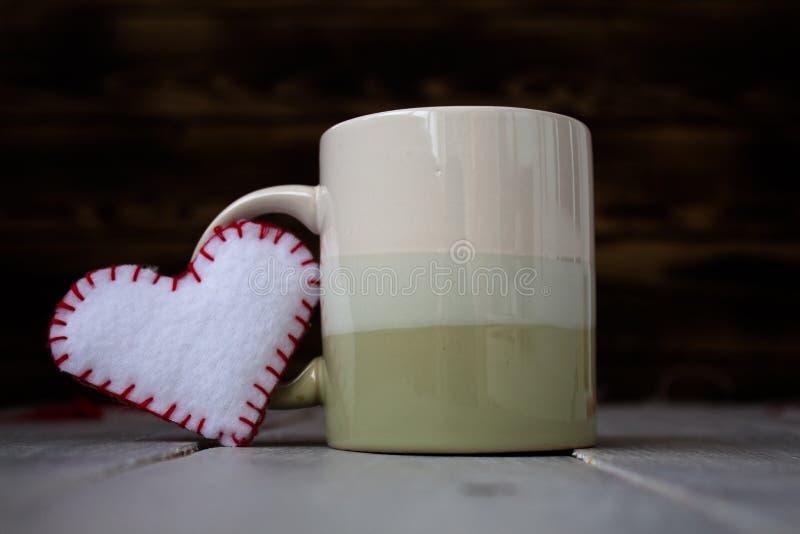 杯和心脏在木板 免版税库存图片