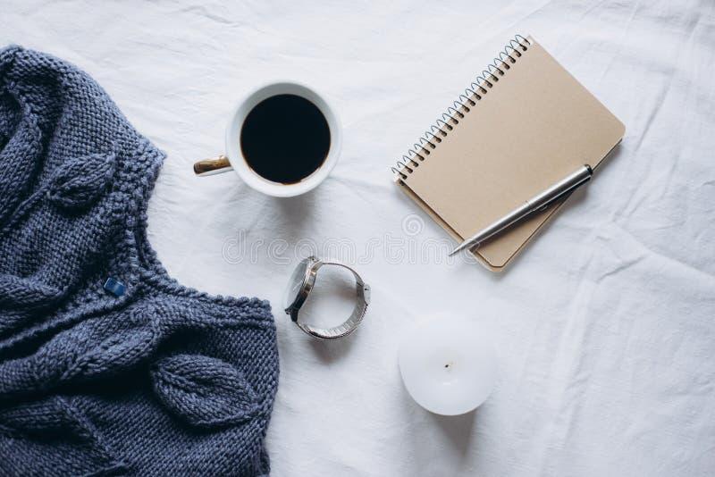 杯咖啡,蓝色被编织的毛线衣,有笔的,时钟,在床上的蜡烛,顶视图笔记本 免版税图库摄影