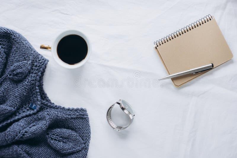 杯咖啡,蓝色被编织的毛线衣,有笔的,时钟,在床上的蜡烛,顶视图笔记本 库存照片