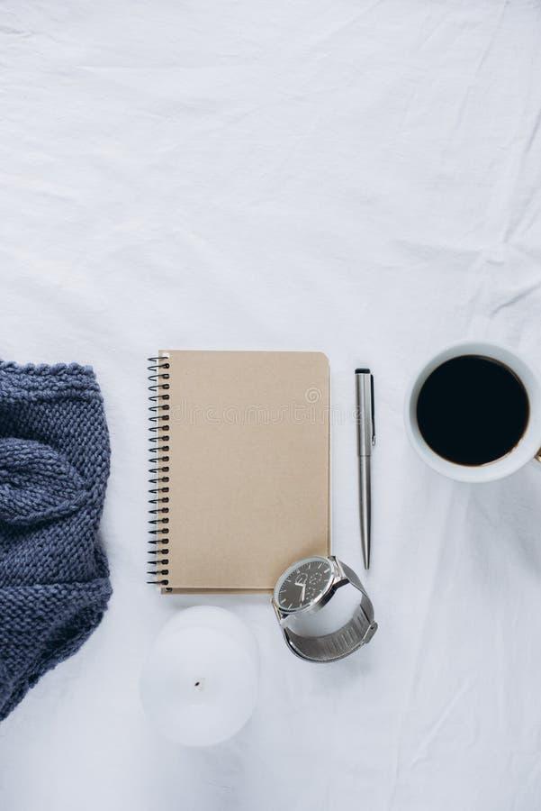 杯咖啡,蓝色被编织的毛线衣,有笔的,时钟,在床上的蜡烛,顶视图笔记本 免版税库存照片