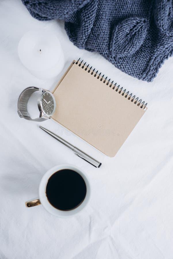 杯咖啡,蓝色被编织的毛线衣,有笔的,时钟,在床上的蜡烛,顶视图笔记本 免版税库存图片