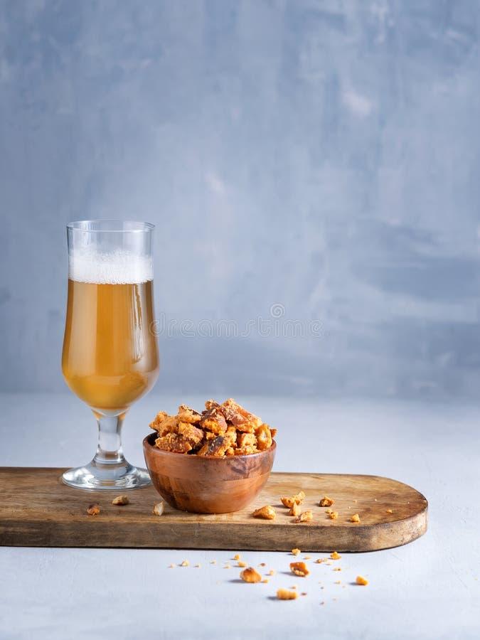 杯啤酒和椒盐脆饼在轻的背景的片快餐与您的空间文本 库存图片