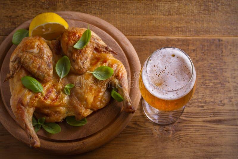 杯啤酒和烤鸡 被烘烤的和水多的鸡是好食物到杯强麦酒 啤酒和肉 免版税库存图片