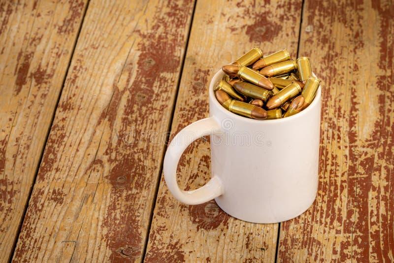 杯在一张木桌上的子弹 图库摄影