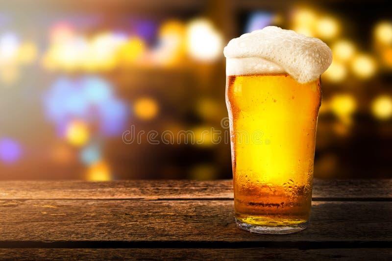 杯在一张桌上的啤酒在bokeh背景的一个酒吧 库存照片