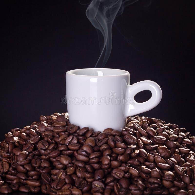 杯在咖啡豆顶部的热的咖啡有黑背景 免版税库存图片