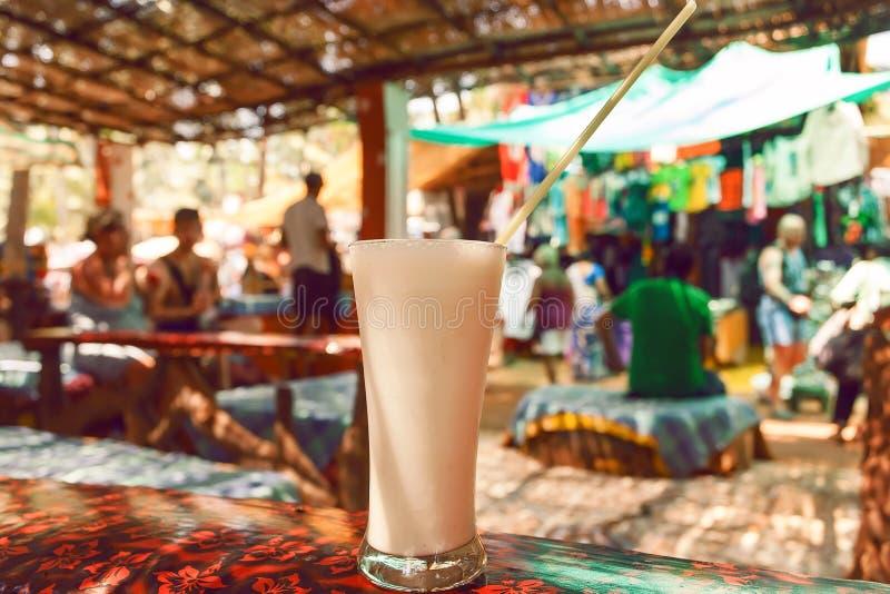杯在咖啡馆桌上的白色乳脂状的牛奶饮料香蕉Lassi在果阿,印度 免版税图库摄影