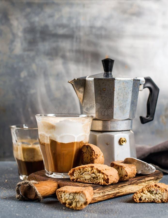 杯在土气木板、cantucci饼干和钢意大利人Moka罐,灰色背景的拿铁咖啡 免版税库存照片