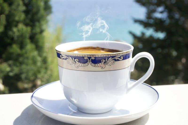 杯在大阳台的热的咖啡与被弄脏的海和树在背景中 免版税库存照片