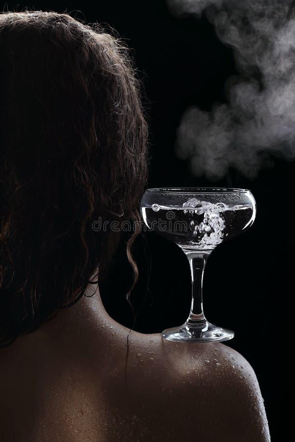 杯在女孩的肩膀的开水 库存图片