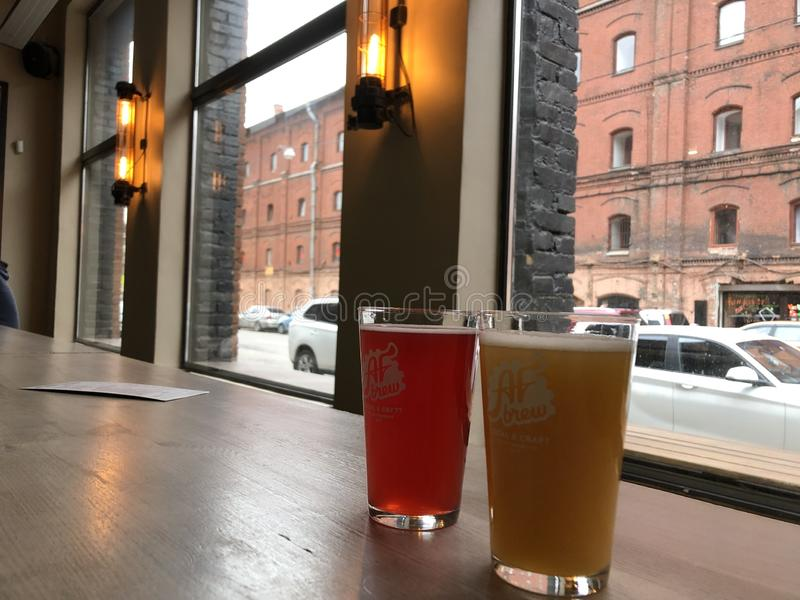杯在客栈背景的淡和黑啤酒 免版税库存图片