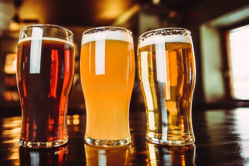 杯在客栈背景的淡和黑啤酒 库存图片