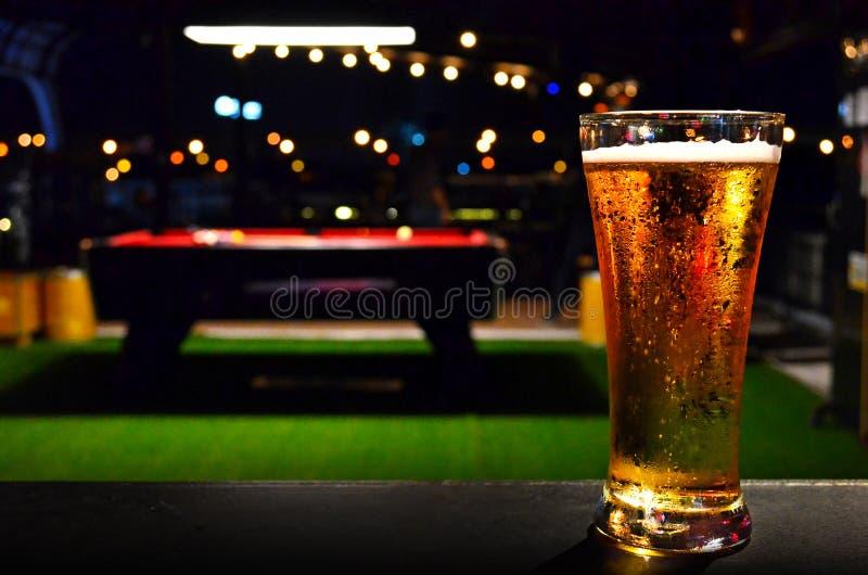 杯在撞球台背景的啤酒 免版税库存照片