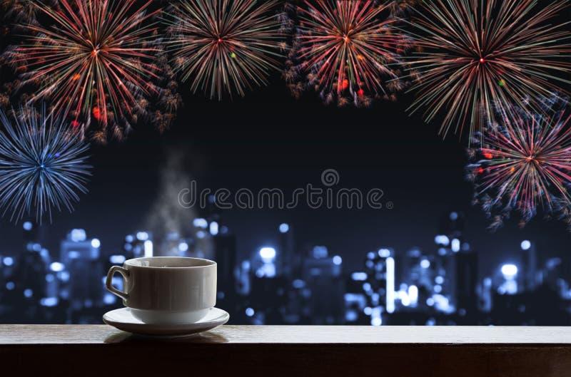 杯在木书桌上的热的饮料与新年庆祝烟花,大厦蓝色defocus Bokeh光在城市 库存照片