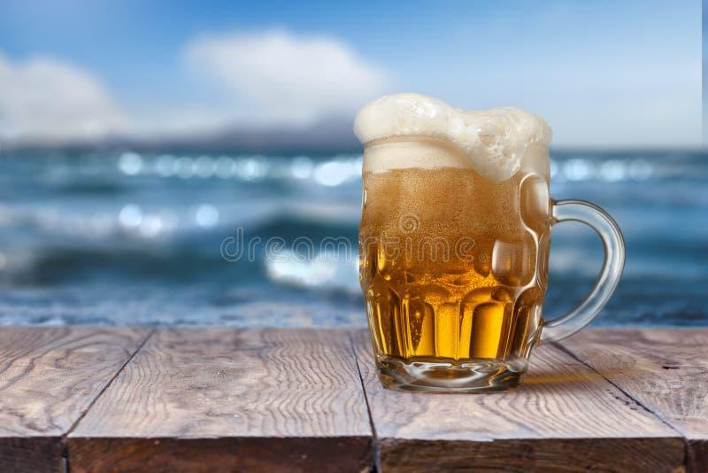 杯在木桌上的啤酒与背景的海 库存照片