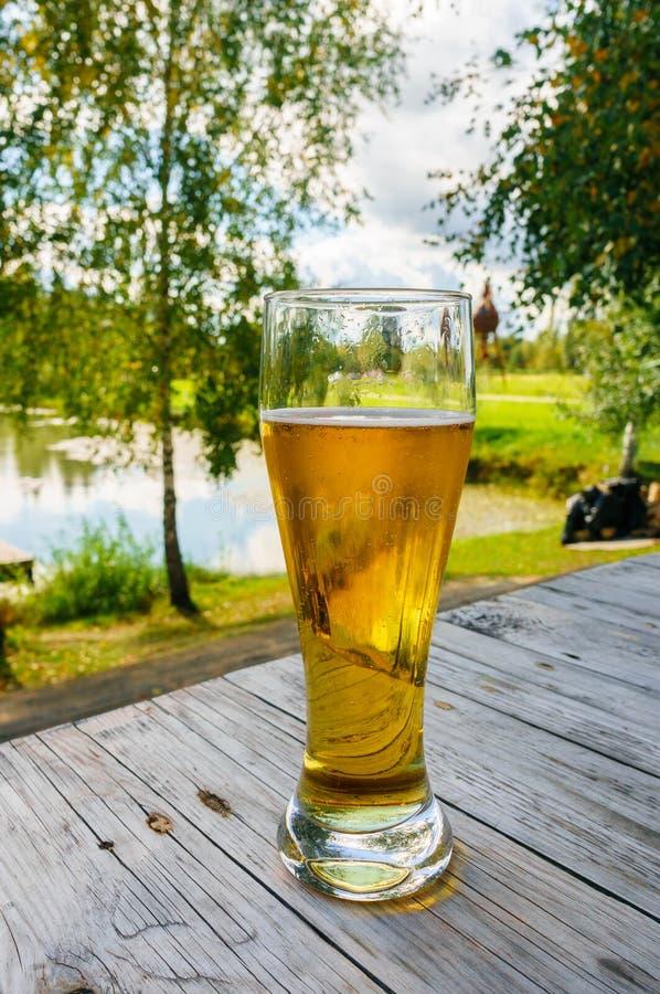 杯在木桌上的啤酒反对冬天自然背景 免版税库存图片