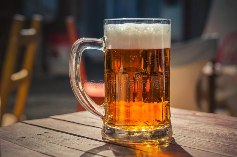 杯在木桌上的啤酒 免版税库存图片