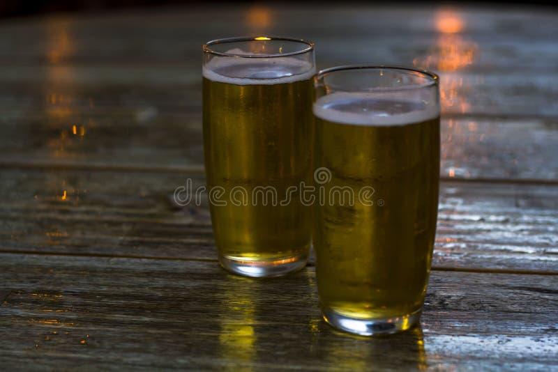 杯在木桌上的啤酒 免版税库存照片