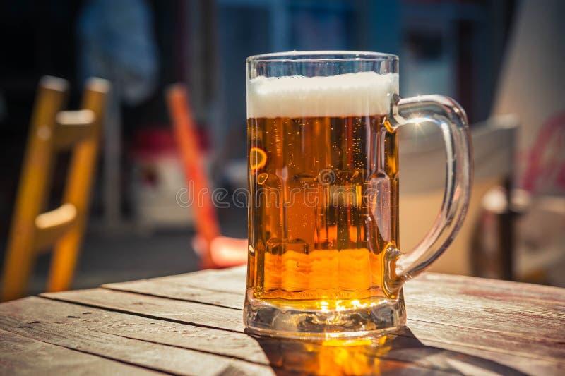 杯在木桌上的啤酒 免版税图库摄影
