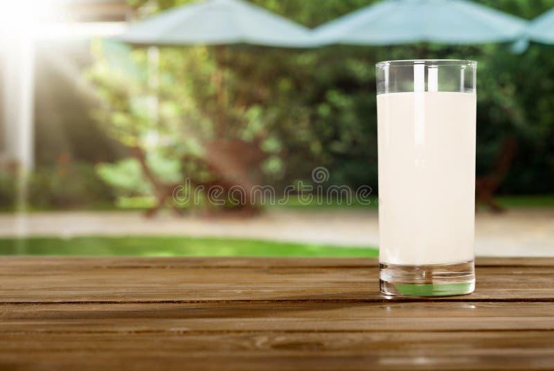 杯在木桌上的新鲜的牛奶 免版税库存照片