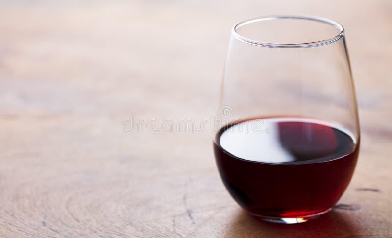 杯在木桌上的红酒 r ?? 免版税库存照片