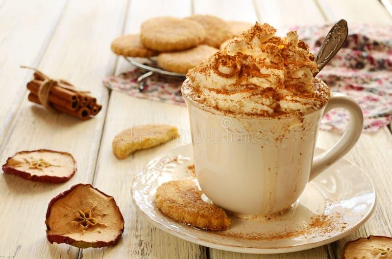 杯在木桌上的被鞭打的奶油色咖啡和苹果曲奇饼 免版税库存图片
