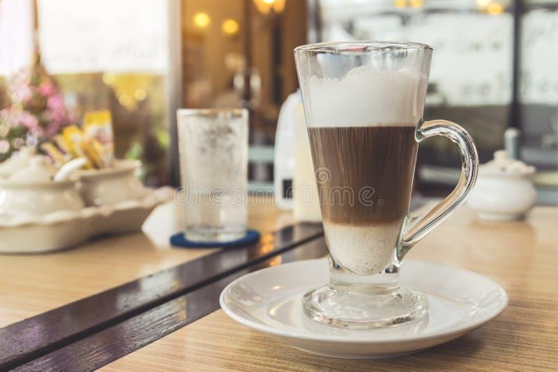 杯在桌上的热的拿铁咖啡在咖啡馆 免版税库存照片