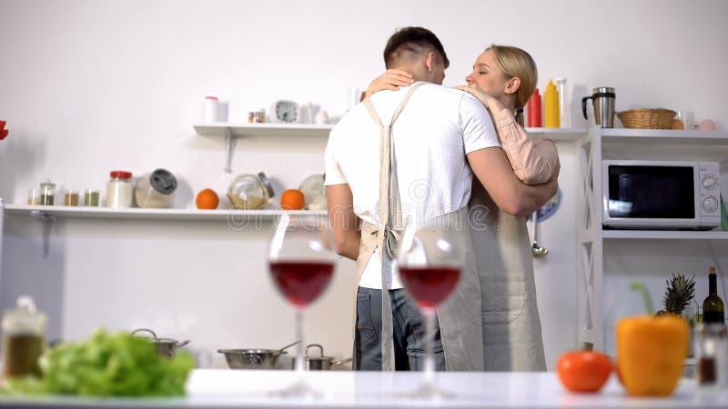 杯在桌,在背景,浪漫晚上的逗人喜爱的夫妇跳舞上的酒 免版税图库摄影