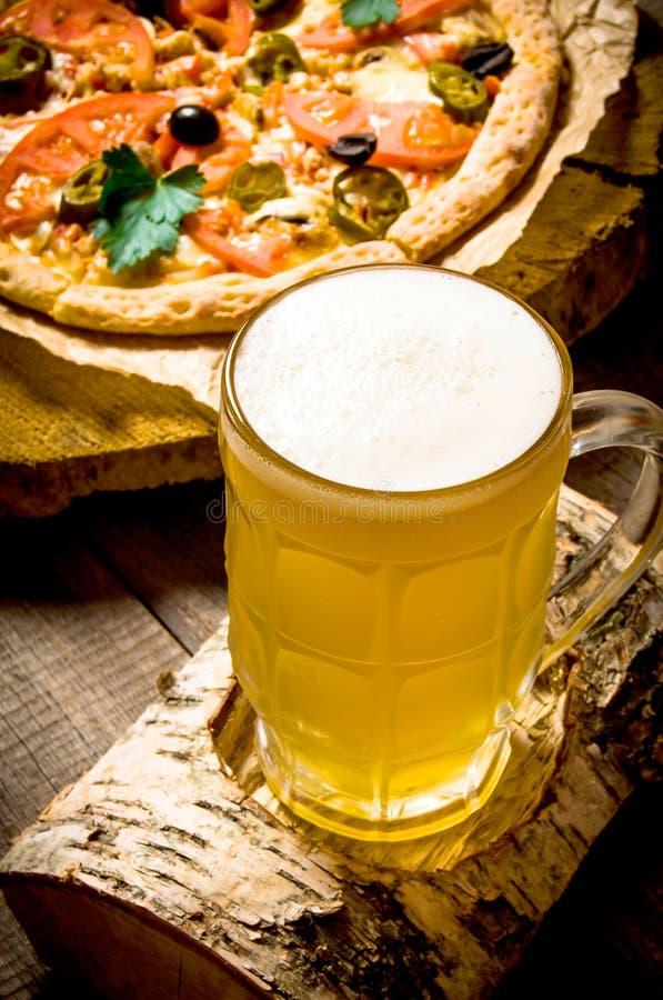 杯在桦树立场的啤酒和在木桌上的薄饼 图库摄影