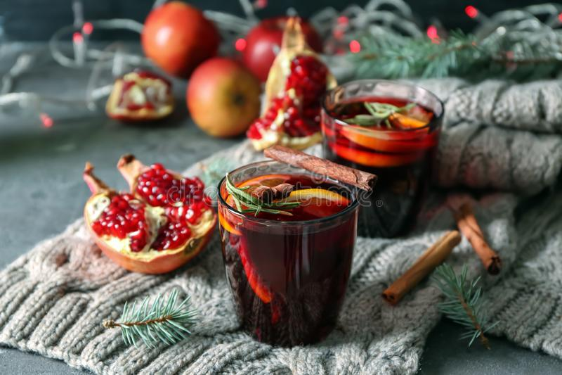 杯在温暖的格子花呢披肩的可口加香料的热葡萄酒 免版税库存照片