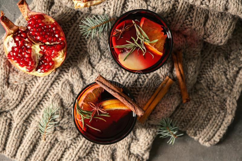 杯在温暖的格子花呢披肩的可口加香料的热葡萄酒 免版税库存图片