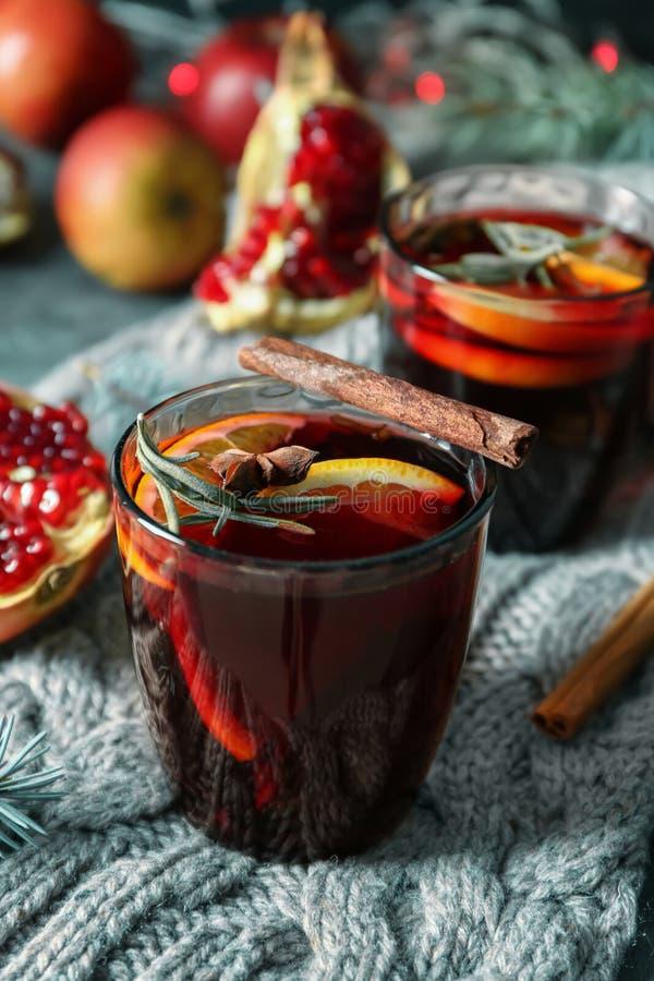 杯在温暖的格子花呢披肩的可口加香料的热葡萄酒 图库摄影