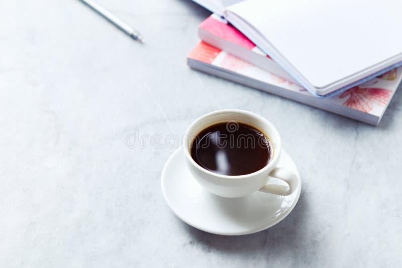 杯在灰色大理石背景的无奶咖啡;书和笔记本在背景中 免版税库存照片