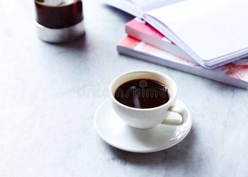 杯在灰色大理石背景的无奶咖啡;书和笔记本在背景中 库存照片