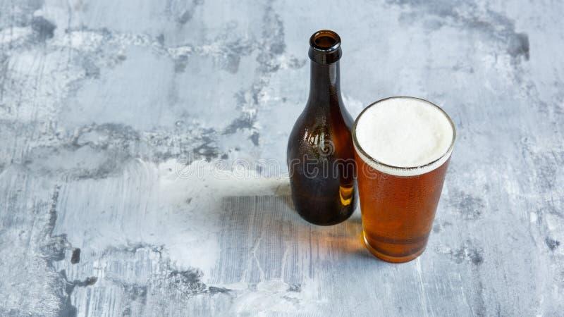 杯在白色石背景的低度黄啤酒 库存照片